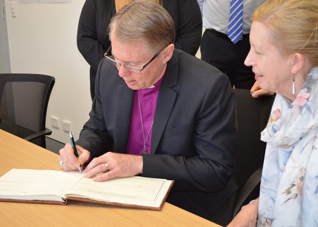 Achbishop signing guest book